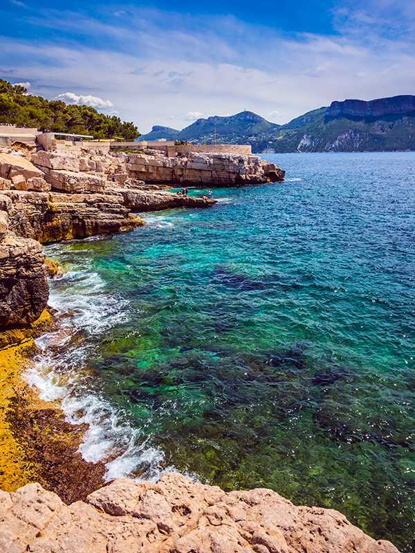 Abrupt stony coast and turquoise sea surface. National Park Calanques on the Mediterranean coast