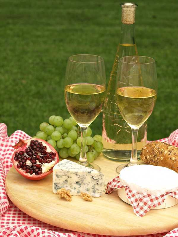 Cheeseboard with cheese, fruits and bottle of white wine