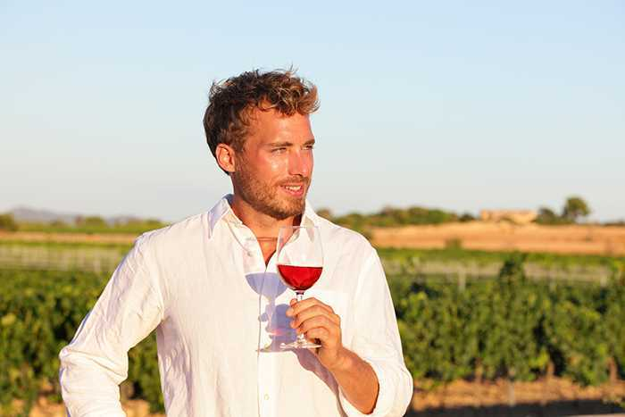 Winemaker man drinking rose or red wine at vineyard from wine glass outdoors